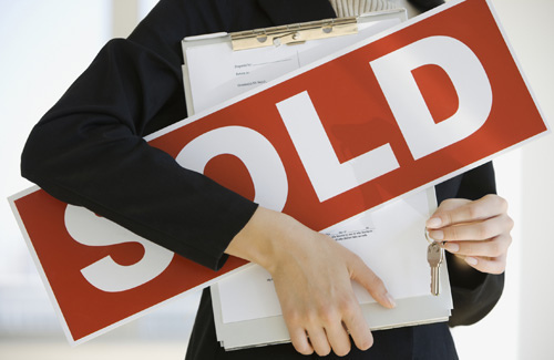 Realtor Holding Sold Sign